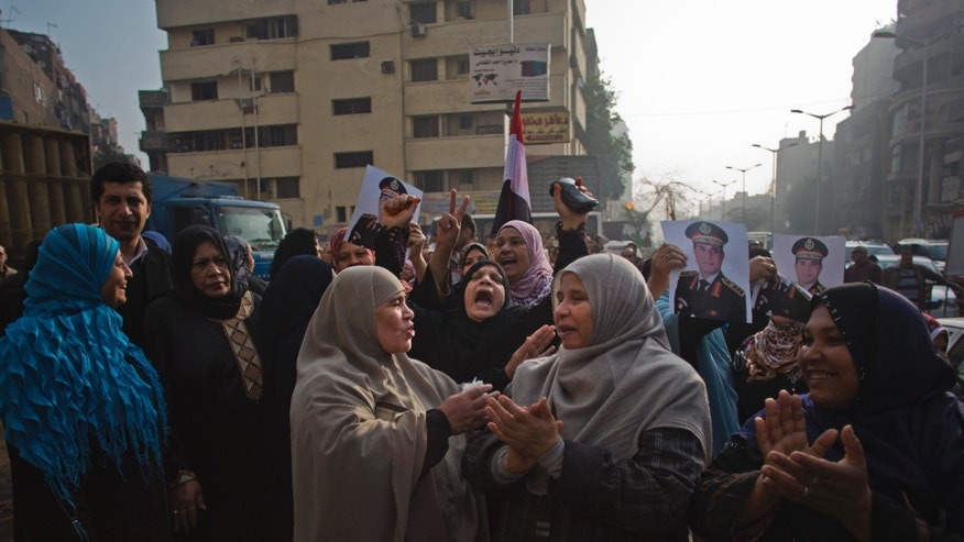 Egyptians chant slogans while holding pictures of Egypt's Defense Minister, Gen. Abdel-Fattah el-Sissi as they gather near the Imbaba courthouse after an early morning explosion damaged the building, in Cairo, Egypt, Tuesday, Jan. 14, 2014. The courthouse was not a polling station and no one was reported injured in the blast.  Egyptians have started voting on a draft for their country's new constitution that represents a key milestone in a military-backed roadmap put in place after President Mohammed Morsi was overthrown in a popularly backed coup last July. (AP Photo/Khalil Hamra)