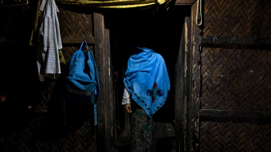 FILE -  In this Sept. 15, 2013 photo, a woman who claims she was raped by Myanmar security forces stands in her home in Ba Gong Nar village, Maungdaw, northern Rakhine state, Myanmar. Myanmar's transition to democracy following five decades of brutal military rule has won widespread international praise, but rights' groups say little has changed in resource-rich border areas, where the army continues to grapple with stubborn ethnic insurgencies. As in the past, the use of sexual violence against civilians is widespread and systematic, said Tin Tin Nyo, general secretary of the Women's League of Burma. (AP Photo/Gemunu Amarasinghe, File)