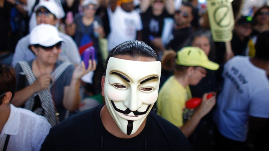 A demonstrator wearing a Guy Fawkes mask joins a teacher's protest outside the Department of Labor in San Juan, Puerto Rico, Wednesday, Jan. 15, 2014.  Striking school teachers are gathering in Puerto Rico's capital to talk with government officials about recent changes to their retirement system as part of a two-day walkout. (AP Photo/Ricardo Arduengo)