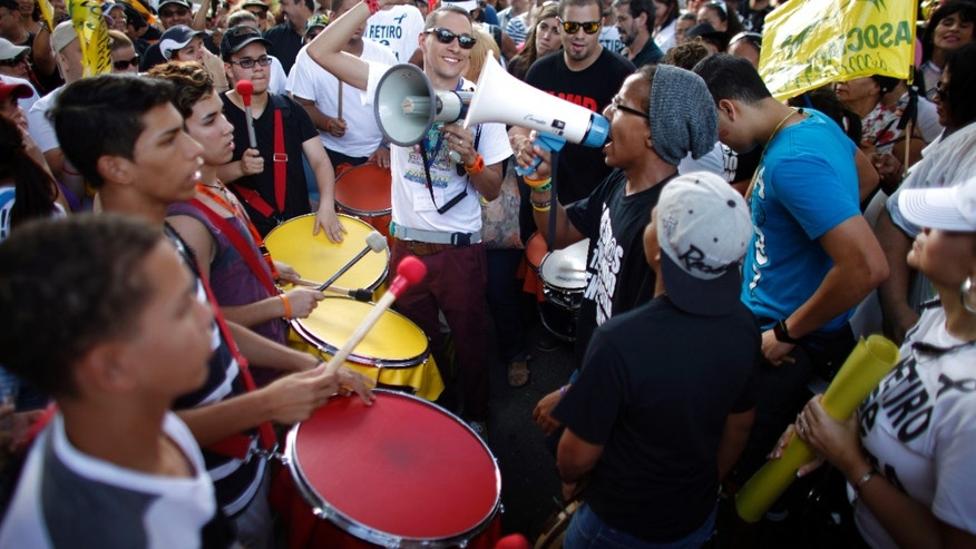 Demonstrators chants during a teacher's protest outside the Department of Labor in San Juan, Puerto Rico, Wednesday, Jan. 15, 2014.  Striking school teachers are gathering in Puerto Rico's capital to talk with government officials about recent changes to their retirement system as part of a two-day walkout. (AP Photo/Ricardo Arduengo)