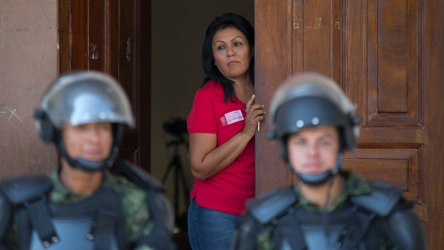 A city employee looks out from a City Hall Hall doorway as a cordon of soldiers guard the government building in Apatzingan, Mexico, Tuesday, Jan. 14, 2014. Mexican soldiers and federal police kept a tense standoff with vigilantes Tuesday after a new government campaign to stop violence in the western Michoacan state turned deadly. A clash occurred as the government sent more troops to where the vigilantes have been fighting the Knights Templar cartel. Federal and state officials met late Tuesday with leaders of vigilante groups but failed to reach a disarmament agreement. (AP Photo/Eduardo Verdugo)