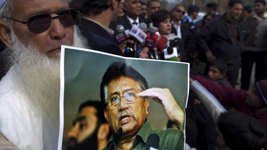 January 16, 2014: A supporter of Pakistan's former president and military ruler Pervez Musharraf holds a poster with a photo of him during a news conference with Musharraf's lawyers outside the special court in Islamabad. (AP Photo/B.K. Bangash)