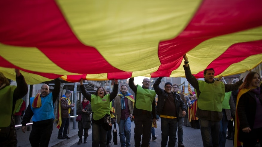"In this photo taken on Sunday, Jan. 12, 2014, people hold a huge ""estelada"" flag during a pro-independence event in Barcelona, Spain. After years of mass protests by Catalans demanding the right to decide whether they want to break away from Spain and form a new European nation, the wealthy northeastern region's lawmakers vote to ask permission from Spanish authorities to hold a secession referendum in November. The request eight months ahead of a Scottish independence referendum is certain to be denied by the central government in Madrid but is virtually guaranteed of generating even more separatist fervor.  (AP Photo/Emilio Morenatti)"