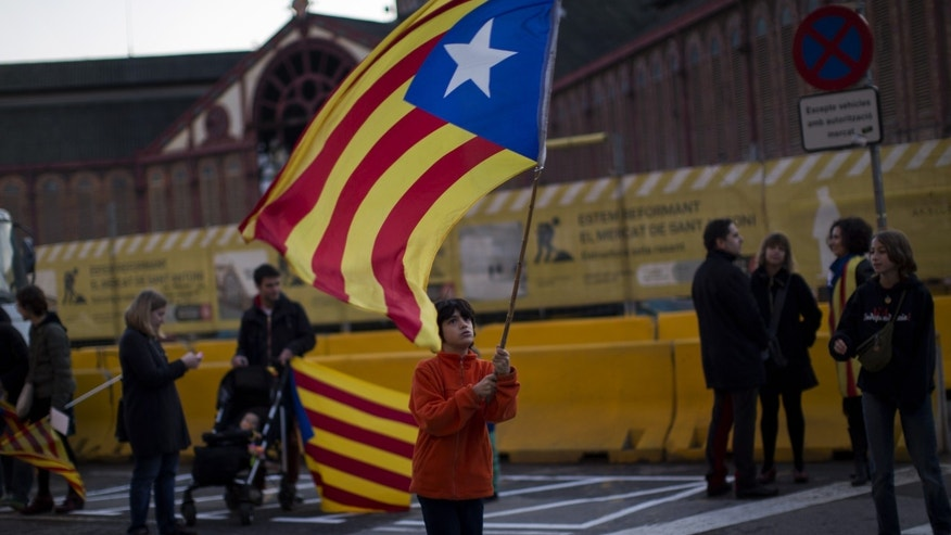 "In this photo taken on Sunday, Jan. 12, 2014, a boy waves an ""estelada"" flag during a pro-independence event to celebrate the Catalan National Day that commemorates the takeover of Catalonia by Spanish troops in 1714, in Barcelona, Spain. After years of mass protests by Catalans demanding the right to decide whether they want to break away from Spain and form a new European nation, the wealthy northeastern region's lawmakers vote to ask permission from Spanish authorities to hold a secession referendum in November. The request eight months ahead of a Scottish independence referendum is certain to be denied by the central government in Madrid but is virtually guaranteed of generating even more separatist fervor.  (AP Photo/Emilio Morenatti)"