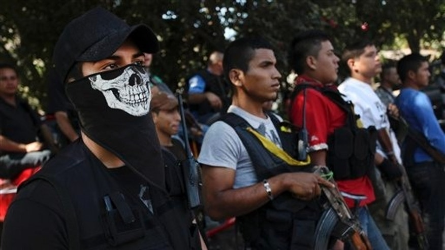 Men belonging to the Self-Defense Council of Michoacan, (CAM), stand at attention during the burial of Mario Perez at a cemetery in Antunez, Mexico, Wednesday, Jan. 15, 2014. Perez was one of the three civilians killed a day earlier by federal forces after they tried to disarm men belonging to a self-defense group that is fighting to rid the Knights Templar drug cartel in a region of Michoacan state known as Tierra Caliente. (AP Photo/Felix Marquez)