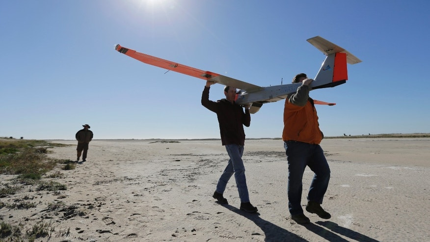 Crew members carry a drone with the wing span of almost 13 feet following a test flight at a ranch near Sarita, Texas,  Wednesday, Jan. 15, 2014. A Texas A&M Corpus Christi research team is conducting tests to help determine how unmanned aircraft system can be integrated into existing airspace. (AP Photo/Eric Gay)