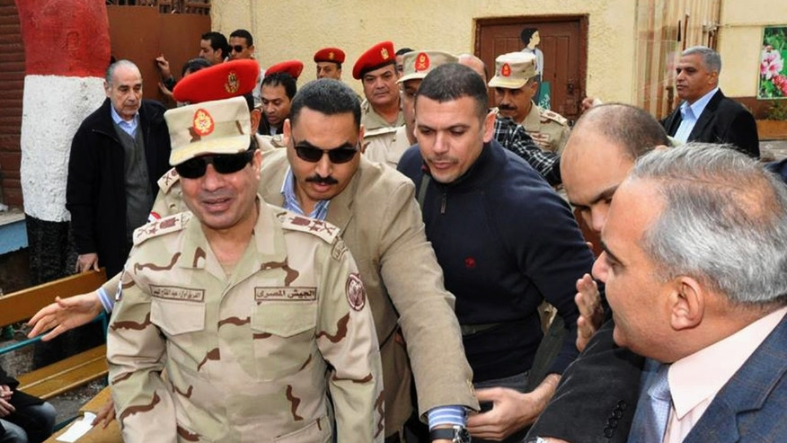 FILE - In this Tuesday, Jan. 14, 2014 file photo released by the Egyptian Defense Ministry, Defense Minister Gen. Abdel-Fattah el-Sissi, left, visits a polling site in the Heliopolis neighborhood of Cairo, Egypt, on the first day of voting in the constitutional referendum. Having secured victory in a referendum on a relatively liberal constitution that he championed, insiders say Egypt's military chief is turning his attention to the country's overwhelming array of problems _ from health and education to government subsidies and investment. The revelations offer the latest indication that Gen. Abdel-Fattah el-Sissi is planning a run for president, capping a stunning transformation for the 59-year-old who started in the infantry.(AP Photo/Egyptian Defense Ministry via Facebook, File)