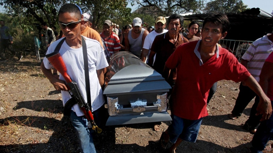 Men carry the coffin that contain the remains of Mario Perez as they prepare to bury him in Antunez, Mexico, Wednesday, Jan. 15, 2014. Perez was one of the three civilians killed a day earlier by federal forces after they tried to disarm men belonging to a self-defense group that is fighting to rid the Knights Templar drug cartel in a region of Michoacan state known as Tierra Caliente. (AP Photo/Felix Marquez)