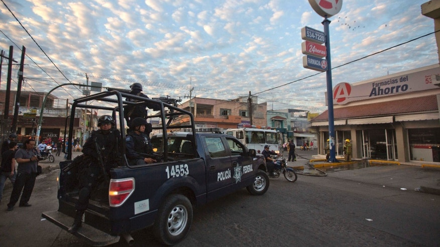 Federal police arrive to a burned pharmacy in the town of Apatzingan in Michoacan state, Mexico, Wednesday, Jan. 15, 2014. Federal forces struggled to bring order to western Mexico as vigilantes battled a drug cartel, but the drug gangs appeared to be carrying business as usual Wednesday. In Apatzingan, attackers doused a pharmacy with gasoline, ordered employees out and set it afire, apparently to enforce a drug cartels orders that no businesses should open. (AP Photo/Eduardo Verdugo)