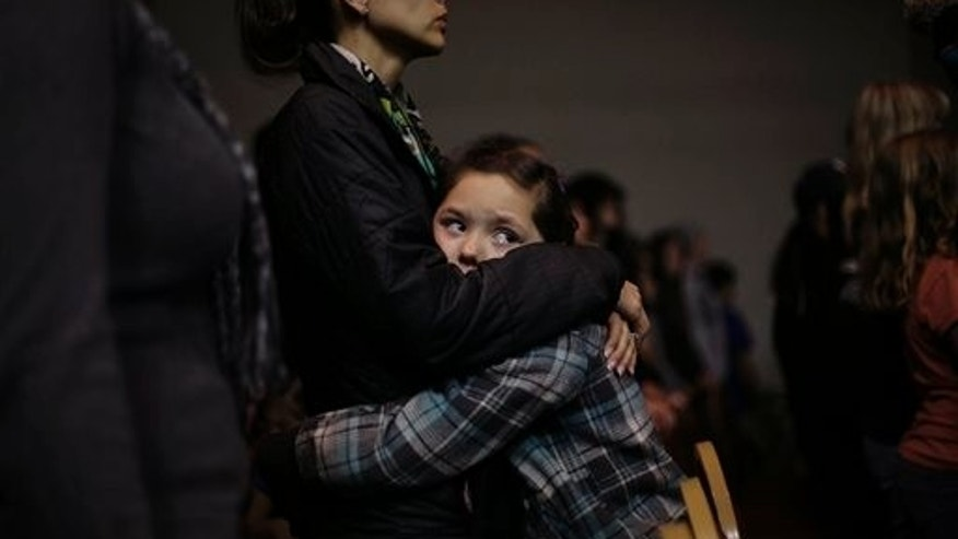 Nine year old Raelynn Holloway, hugs her mother Rhiannon Holloway in Roswell, N.M., Tuesday Jan. 14, 2014.
