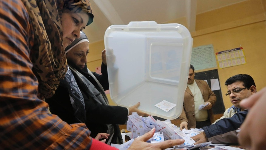 Election workers empty a ballot box at the end of the second, final day of a key referendum on a new constitution, inside a polling station in Cairo, Egypt, Wednesday, Jan. 15, 2014. The vote is a milestone in a military-backed political roadmap toward new elections for a president and a ballot-box test of public opinion on the coup that removed Islamist President Mohammed Morsi and his Muslim Brotherhood from power last July. (AP Photo/Amr Nabil)