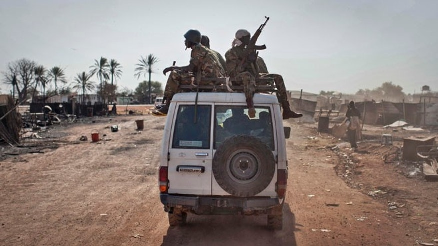 Jan. 12, 2014: In this file photo, South Sudanese government forces ride on a vehicle through the still-smoldering town, after government forces on Friday retook from rebel forces the provincial capital of Bentiu, in Unity State, South Sudan.