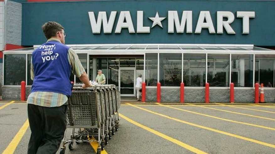 A Wal-Mart employee pushes a line of shopping carts toward the entrance of a store, in Walpole, Mass.