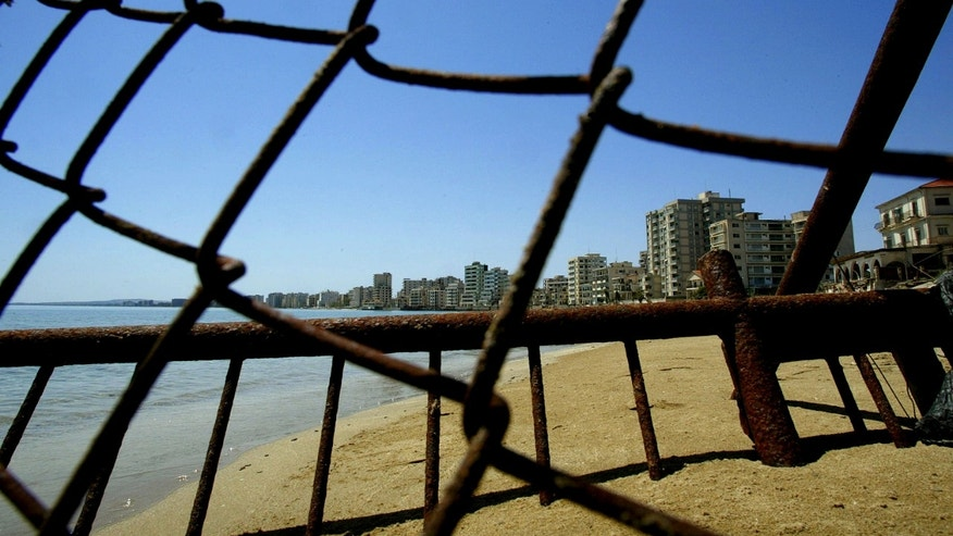 FILE - In this Monday, May 5, 2003 file photo deserted hotels in an area used by the Turkish military are seen through a wire fence in the Turkish-occupied area in the abandoned coastal city of Varosha,  in southeast of the island of Cyprus.  Time virtually stopped in 1974 for the Mediterranean tourist playground of Varosha. When Turkey invaded Cyprus in the wake of a coup by supporters of union with Greece, thousands of residents fled, and chain-link fences enclosed a glamorous resort that it's said once played host to Hollywood royalty like Elizabeth Taylor.    (AP Photo/Petros Karadjias, file)