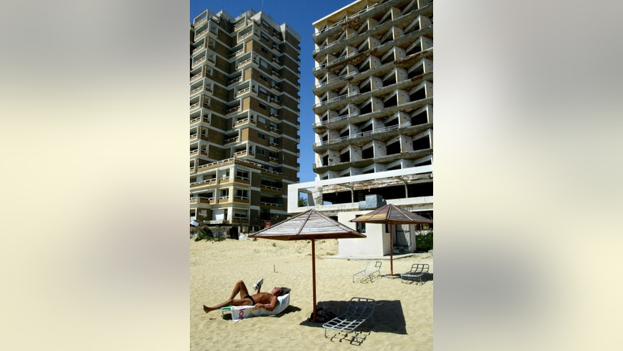 FILE - In this Monday, May 5, 2003 file photo, a tourist reads his book as he sunbathes in front of a destroyed hotel in the Turkish-occupied of abandoned coastal city of Varosha, in southeast of the island of Cyprus. Time virtually stopped in 1974 for the Mediterranean tourist playground of Varosha. When Turkey invaded Cyprus in the wake of a coup by supporters of union with Greece, thousands of residents fled, and chain-link fences enclosed a glamorous resort that it's said once played host to Hollywood royalty like Elizabeth Taylor.  (AP Photo/Petros Karadjias, file)