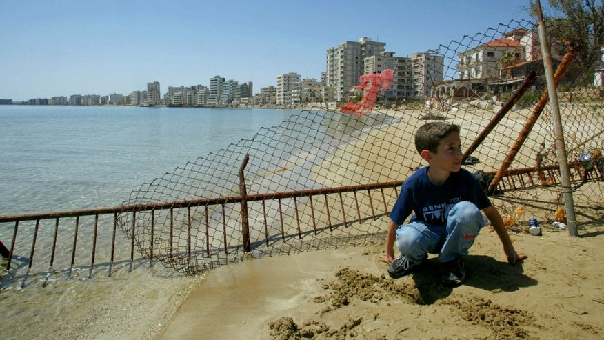 FILE - In this Monday, May 5, 2003 file photo, a Greek Cypriot boy sits on a beach in front of deserted hotels in an area used by the Turkish military, seen in distance, in the Turkish-occupied abandoned coastal city of Varosha, in southeast of island of Cyprus. Time virtually stopped in 1974 for the Mediterranean tourist playground of Varosha. When Turkey invaded Cyprus in the wake of a coup by supporters of union with Greece, thousands of residents fled, and chain-link fences enclosed a glamorous resort that it's said once played host to Hollywood royalty like Elizabeth Taylor.    (AP Photo/Petros Karadjias, file)