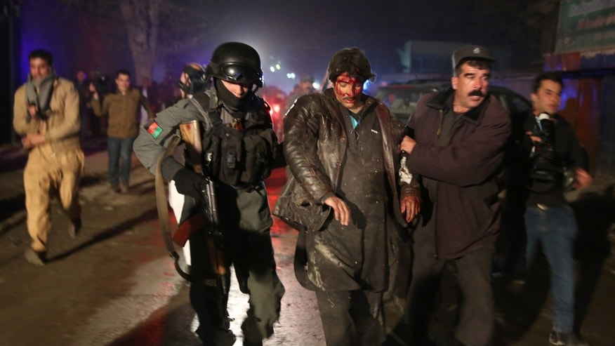Afghan police forces assist an injured man at the site of an explosion in Kabul, Afghanistan, Friday, Jan. 17, 2014. Afghan police said a suicide bomber attacked a Kabul restaurant popular with foreigners, officials. (AP Photo/Massoud Hossaini)