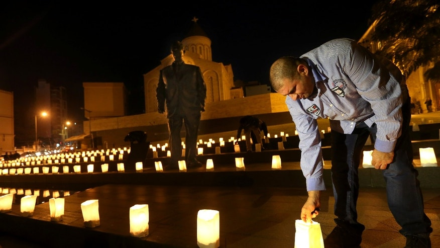 "A supporter of slain former Lebanese Prime Minister Rafik Hariri lights candle during a vigil in front of Hariri's statue, in Beirut, Lebanon, Thursday, Jan. 16, 2014. Nearly nine years after a truck bomb killed Hariri and 22 others, the trial started Thursday for four Hezbollah suspects accused of plotting the assassination that turned a Beirut seaside street into a ""man-made hell."" (AP Photo/Hussein Malla)"