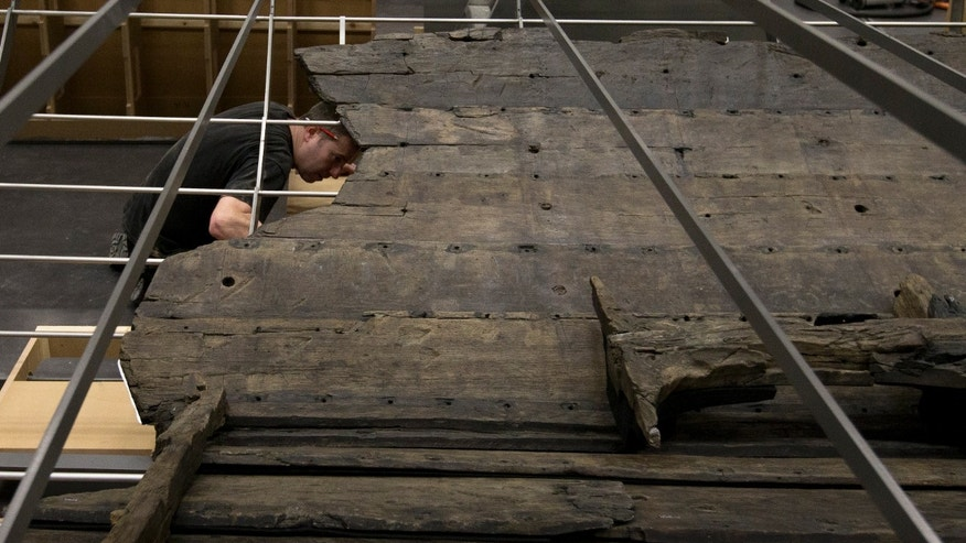 A conservator helps with the final assembly of The Viking ship known as Roskilde 6, of which about 20 per cent of the timber remains and which is dated to around 1025 AD, at the British Museum in London, Friday, Jan. 17, 2014. The ship was excavated from the banks of Roskilde Fjord, Denmark in 1997. It will be part of a Viking exhibition at the museum that will open to the public on March. 6, 2014. (AP Photo/Alastair Grant)