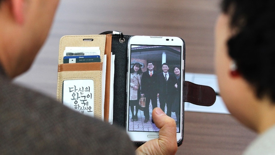In this Friday, Jan. 9. 2014 photo, Jeon Jang-Beom, left, and Yoon Hyun-Jin show their family photo taken with their son Jeon Seong-Jin, second from left in the picture, during an interview in Seoul, South Korea. Jeon Seong-Jin, a 26-year-old dentist, is being punished for a crime that is not a crime at all in most of the world. A Jehovah's Witness, he has refused to become a soldier in South Korea, where all able-bodied male citizens are required to serve about 21 months in the army. More than 660 conscientious objectors were jailed each year in South Korea from 2004 to 2012, far more than any other country. Eritrea comes in second with only about 50 imprisoned, according to the official website of Jehovah's Witnesses, who often refuse military service because they believe the Bible forbids warfare. (AP Photo/Ahn Young-joon)