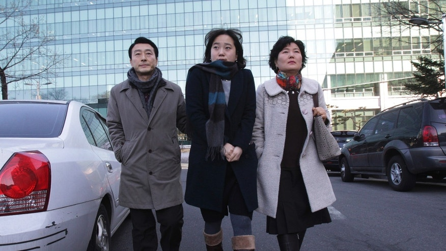 In this Friday, Jan. 9. 2014 photo, parents Jeon Jang-Beom and Yoon Hyun-Jin with their daughter Jeon Ji-Hye, center, leave Seoul High Court after attending their son Jeon Seong-Jin's trial, in Seoul. Jeon Seong-Jin, a 26-year-old dentist, is being punished for a crime that is not a crime at all in most of the world. A Jehovah's Witness, he has refused to become a soldier in South Korea, where all able-bodied male citizens are required to serve about 21 months in the army. More than 660 conscientious objectors were jailed each year in South Korea from 2004 to 2012, far more than any other country. Eritrea comes in second with only about 50 imprisoned, according to the official website of Jehovah's Witnesses, who often refuse military service because they believe the Bible forbids warfare. (AP Photo/Ahn Young-joon)