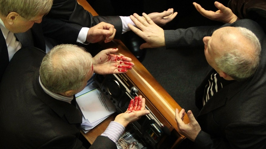 Ukrainian pro-government lawmaker Volodymyr  Malyshev, left, wipes blood from his face after a scuffle in the Ukrainian parliament  in Kiev, Ukraine, Thursday, Jan. 16, 2014. Lawmakers scuffled in the Ukrainian parliament during a debate on this year's budget. Despite the opposition's efforts to disrupt the vote,  the budget draft, which has already been delayed by almost two months, was passed in its second reading. (AP Photo/Sergei Chuzavkov)