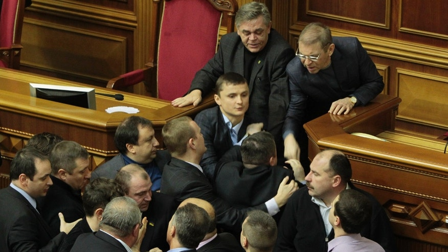 Ukrainian lawmakers scuffle in the Ukrainian parliament in Kiev, Ukraine, Thursday Jan. 16, 2014. Lawmakers scuffled in the Ukrainian parliament during a debate on this year's budget. Despite the opposition's efforts to disrupt the vote, the budget draft, which has already been delayed by almost two months, was passed in its second reading. (AP Photo/Sergei Chuzavkov)