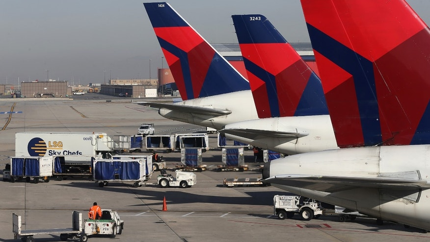 SALT LAKE CITY, UT - NOVEMBER 27: Ground crew personnel service Delta planes at the Salt Lake City international Airport on November 27, 2013 in Salt Lake City, Utah.  A wintry storm system that is covering much of the nation is threatening to wreak havoc on holiday travel . (Photo by George Frey/Getty Images)
