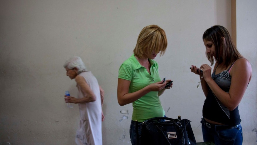In this photo taken Jan. 30, 2013, Cuban Amalia Reigosa, center, gives her phone to her sister Jaynet in Havana, Cuba, before beginning her trip to Milan, Italy. Reigosa is one of the first to take advantage of a travel reform that went into effect a year ago this week in Cuba, when the government scrapped an exit visa requirement that for five decades had made it difficult for most islanders to go abroad. (AP Photo/Ramon Espinosa)