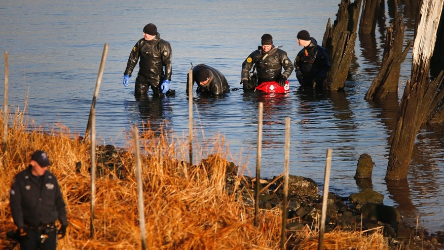 NYPD dive unit searches for human remains along a rocky shoreline in Queens, New York, Friday, Jan. 17, 2014.