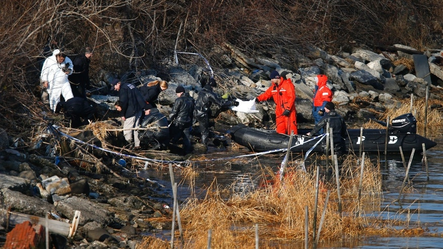 Police continue the search for human remains along a rocky shoreline in Queens, New York, Friday, Jan. 17, 2014.