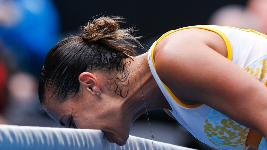Flavia Pennetta of Italy bites the net in frustration during her fourth round match against Angelique Kerber of Germany at the Australian Open tennis championship in Melbourne, Australia, Sunday, Jan. 19, 2014.(AP Photo/Eugene Hoshiko)
