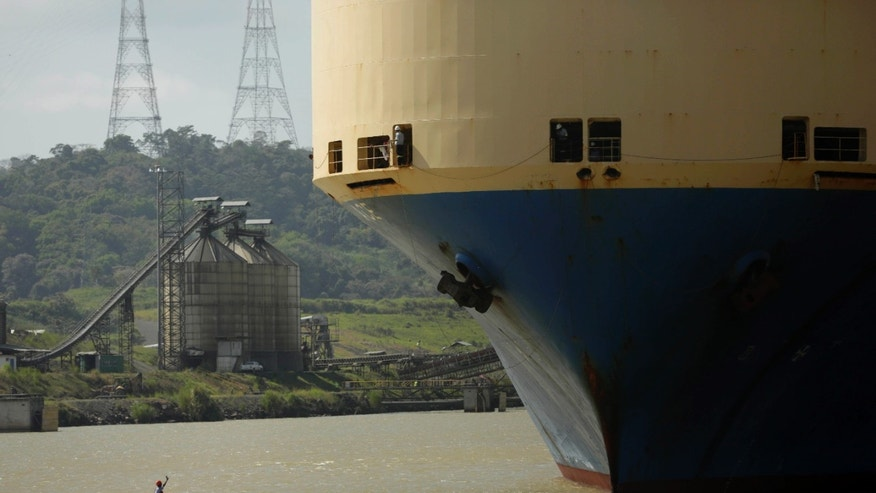 In this Jan. 14, 2014 photo, a small boat takes in a line of rope from a cargo ship while entering to the Pedro Miguel locks at the Panama Canal near Panama City. The current canal expansion project would double its capacity. (AP Photo/Arnulfo Franco)