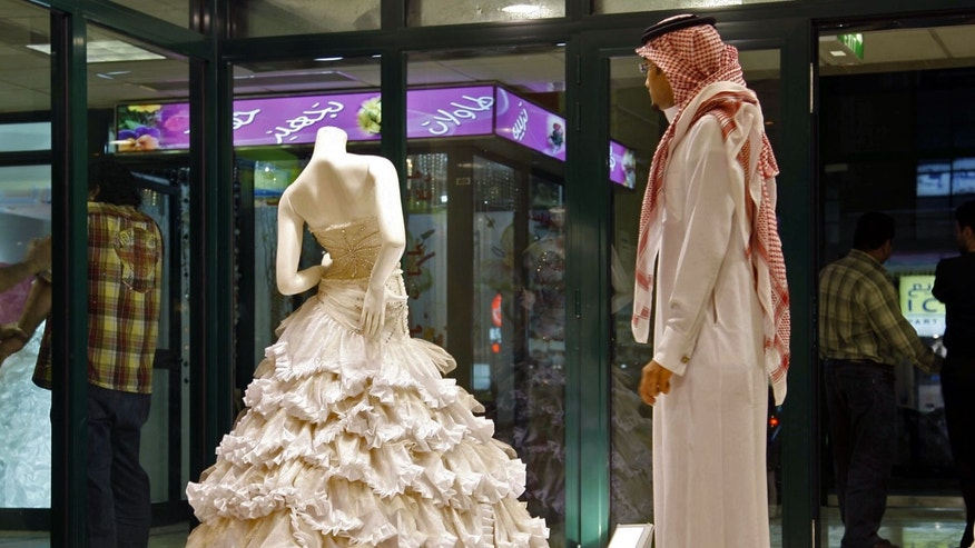 FILE - In this Sunday, Aug. 3, 2008 file photo, a Saudi man stands in front of a wedding dress at a shop in Riyadh, Saudi Arabia. In the Middle East, Saudi Arabia and Yemen are the only Arab countries that do not have laws that set a minimum age for marriage. According to a December 2011 Human Rights Watch report, approximately 14 percent of girls in the Arab world's poorest nation of Yemen were married before the age 15, and 52 percent were married before 18 years old. (AP Photo, File)