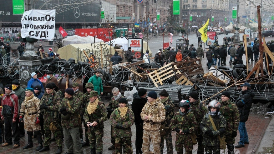 Pro-European Union activists stand in front of a barricade of their tent camp to protect it in downtown Kiev, Ukraine, Saturday, Jan. 18, 2014. About seventy people who oppose demonstrators in Kiev came to the protester's tent camp to destroy it. Ukraine's president on Friday ignored sharp Western criticism and approved controversial anti-protest legislation aimed at quashing massive anti-government demonstrations which have rocked Kiev for nearly two months. A poster at left criticizes Ukrainian judicial system. (AP Photo/Sergei Chuzavkov)