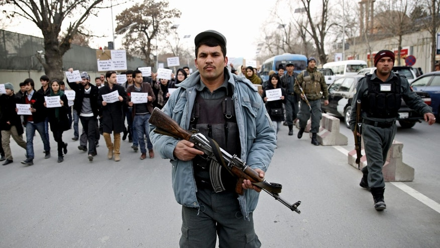 Jan. 19, 2014: An Afghan police walks ahead of members of civil society organizations for their protection as they march in a street, during an anti-terrorism demonstration in Kabul, Afghanistan.