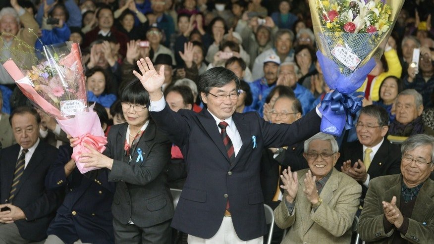 Jan. 19, 2014 - Nago city Mayor Susumu Inamine, center right, and  his wife Ritsuko celebrate after he was re-elected in the mayoral election in Nago, on the southern Japanese island of Okinawa.