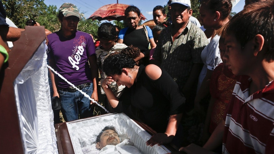 Cristina Cortez cries as she stands in front of the coffin that contain the remains of her father, Juan de Dios Cortez, a former sugarcane cutter of the sugar mill, Ingenio San Antonio, ISA, to a cemetery in Chichigalpa, Nicaragua, Monday, Jan. 20, 2014. Cortez died Saturday after allegedly being shot by police during protests by the cutters demanding compensation for damages to their health resulting from alleged exposure to agrochemicals and pesticides. (AP Photo/Esteban Felix)