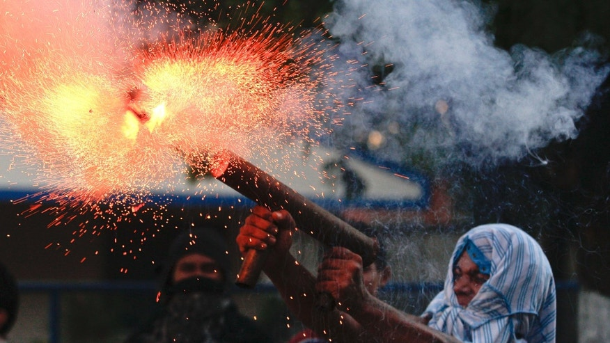 A relative of the former worker of the Ingenio San Antonio, ISA, fires a homemade mortar during  protests in Chichigalpa, Nicaragua, Sunday, Jan. 19, 2014. A former sugarcane cutter died Saturday, after allegedly being shot by police during the confrontations. The former sugarcane cutters were demanding compensation for damages to their health resulting from alleged exposure to agrochemicals and pesticides when the protest turned violent. (AP Photo/Esteban Felix) (AP Photo/Esteban Felix)