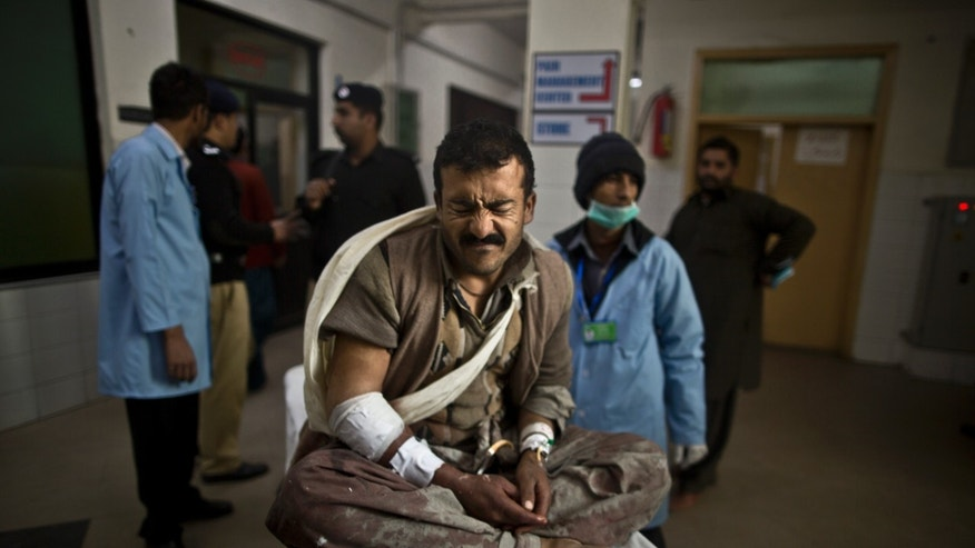 A Pakistani man, who was injured in a suicide bombing, reacts to his pain while waiting on a stretcher in a hospital corridor to be checked by doctors, in Rawalpindi, Pakistan, Monday, Jan. 20, 2014. A Taliban suicide bomber blew himself up not far from Pakistan's military headquarters Monday, killing more than a dozen of people a day after a militants bombing inside an army compound in the northwest of the country, officials and militants said.(AP Photo/Muhammed Muheisen)