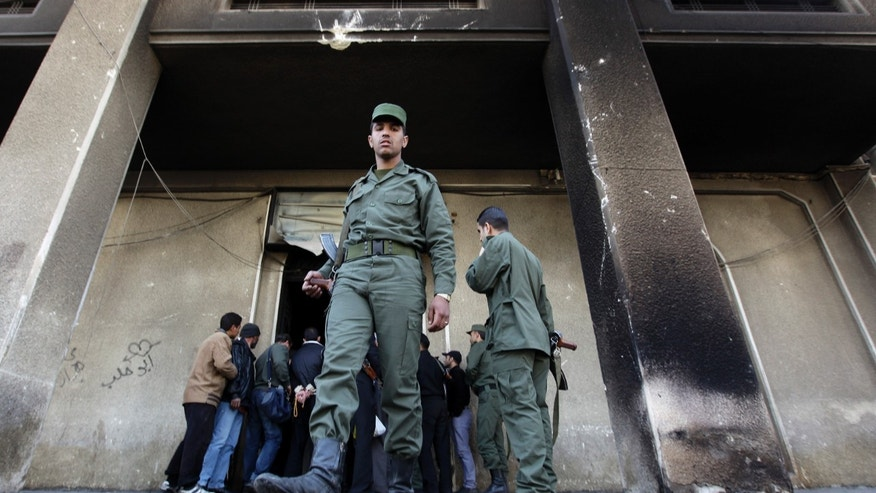 "FILE - In this Monday, March 21, 2011 file photo, A Syrian army soldier steps out from the burned court building that was set on fire by Syrian anti-government protesters, in the southern city of Daraa, Syria. It began innocently enough in March 2011, with a short phrase spray-painted on a schoolyard wall by teenagers in the southern Syrian city of Daraa: ""Your turn is coming, doctor."" The doctor referred to President Bashar Assad, a trained ophthalmologist, and the implication was that he too would fall from power like his counterparts in Tunisia and Egypt who had recently been toppled in popular revolts. Nearly three years after the crisis began, Syria's government and opposition are set to meet in Geneva this week for the first direct talks aimed at ending the conflict. (AP Photo/Hussein Malla, File)"