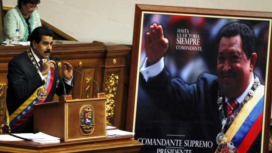 Venezuela's President Nicolas Maduro, left, speaks next to a framed poster featuring the late President Hugo Chavez during the annual state-of-the-nation address to the National Assembly in Caracas, Venezuela, Wednesday, Jan. 15, 2014. (AP Photo/Fernando Llano)