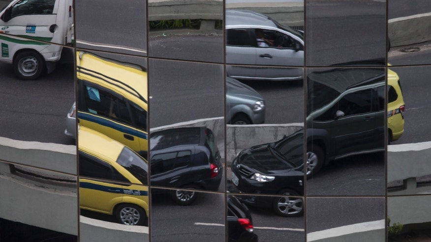 In this Jan. 17, 2014 photo, cars are reflected in a building's windows in Rio de Janeiro, Brazil. Safety experts applauded the government's plan to construct a crash test center as long overdue, though some warn that it is still not enough because Brazil does not require any follow-up inspections to ensure vehicles remain safe over time.  (AP Photo/Felipe Dana)