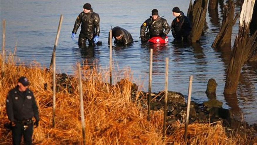 After discovering an arm, torso and legs Thursday, a New York Police Department dive unit continues the search for human remains along a rocky shoreline in the Queens borough of New York, Friday, Jan. 17, 2014.