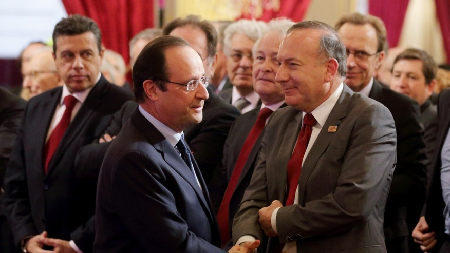 "French President Francois Hollande, left, shakes hand with French employer's body MEDEF union leader Pierre Gattaz at the end of a New Year ceremony for employment sector representatives at the Elysee Palace in Paris, Tuesday, Jan. 21, 2014. French President Francois Hollande warned companies that they have to hire large numbers of French workers, especially the young and old, if they want to benefit from a promised 30-billion-euro cut in payroll taxes. Hollande is counting on his so-called ""responsibility pact"" to revive growth in the stagnant economy and reduce nearly 11 percent unemployment. (AP Photo/Philippe Wojazer, Pool)"