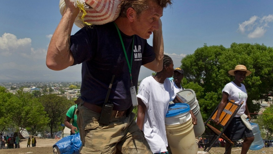 FILE - In this April 10, 2010 file photo, U.S. actor Sean Penn carries the belongings of a person displaced by the 2010 earthquake as people are relocated from the Petion Ville Golf Club to a new camp in Port-au-Prince, Haiti. The camp on the nine-hole golf course once housed thousands of persons, after the devastating earthquake four years ago but that number has since dropped as the several dozen people who remain in the settlement are expected to leave by Friday. (AP Photo/Ramon Espinosa, File)