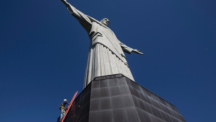 A worker climbs the Christ Redeemer statue to examine recent damage in Rio de Janeiro, Brazil, Tuesday, Jan. 21, 2014. The famed statue is being examined after two fingers and the head were chipped during recent lightning storms. Officials say they'll place more lightning rods on the statue in an effort to prevent future damage. (AP Photo/Felipe Dana)