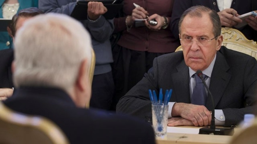 January 17, 2014: Russian Foreign Minister Sergey Lavrov, right, listens to his Syrian counterpart Walid al-Moallem, left, during a meeting in Moscow.