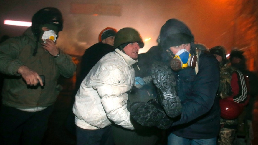 Protesters assist a wounded comrade, in central Kiev, Ukraine, early Tuesday, Jan. 21, 2014. After a night of vicious street battles, anti-government protesters and police clashed again Monday in Ukraine's capital. Hundreds of protesters, many wearing balaclavas, hurled rocks and stun grenades. Police responded with tear gas. (AP Photo/Sergei Grits)