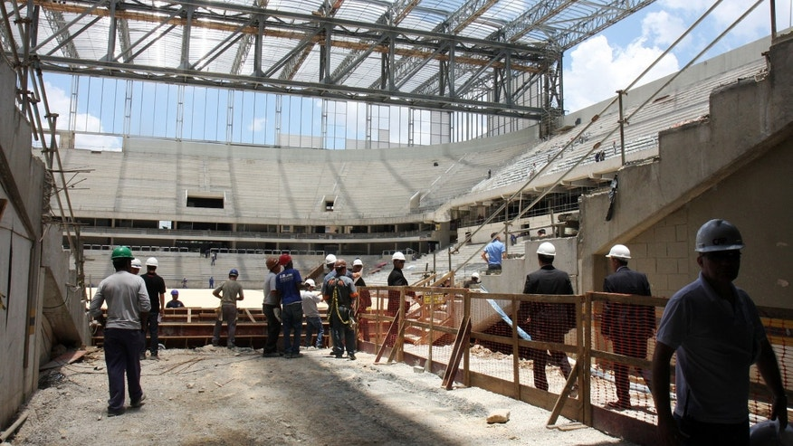 In this photo released by Portal da Copa, workers stand in the Arena da Baixada stadium in Curitiba, Brazil, Tuesday, Jan. 21, 2014. FIFA Secretary General Jerome Valcke is giving Brazilian organizers only a few more weeks to show that the stadium in Curitiba will be ready in time for the World Cup. Most of the delay at the venue, which was about 90 percent completed, was blamed on difficulties getting the needed funding for the construction. The stadium is being built mainly by local club Atletico Paranaense. (AP Photo/Portal da Copa, Paulino Menezes)